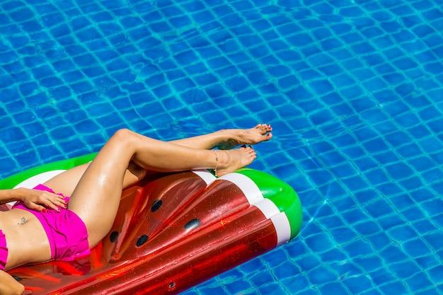 Vista aérea da fêmea no biquini que encontra-se em um colchão de flutuação na piscina.