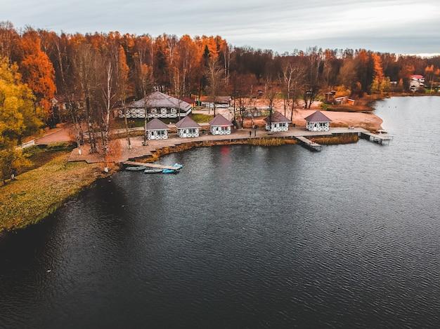 Vista aérea da floresta e do lago azul. casa de sauna à beira do lago. cais de madeira com barcos de pesca. são petersburgo, rússia.
