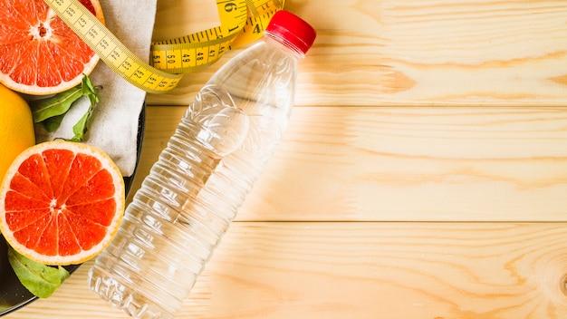 Vista aérea da garrafa; fita métrica e frutas cítricas em fundo de madeira