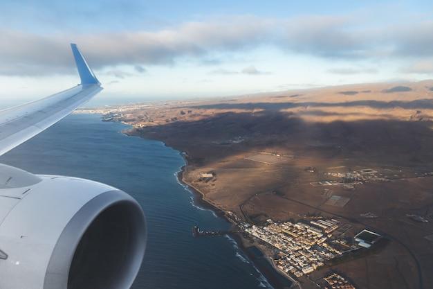 Vista aérea da ilha de gran canaria e a asa do avião a partir da janela. conceito de voos e férias.