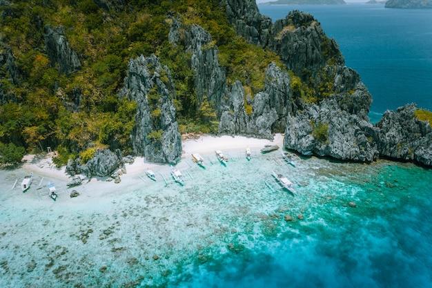 Vista aérea da ilha tropical com barcos turísticos atracados na lagoa. el nido, palawan, filipinas