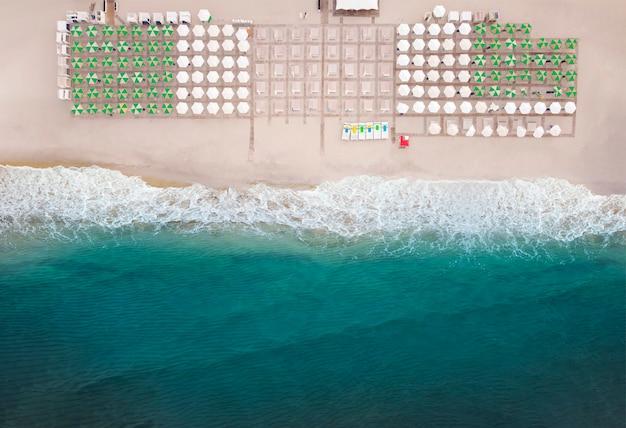 Vista aérea da incrível praia com guarda-sóis e mar azul-turquesa na estação quente de verão.