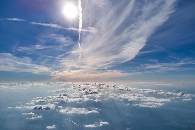 Vista aérea da janela do avião em alta altitude da terra coberta com fina camada branca de névoa enevoada e nuvens distantes.