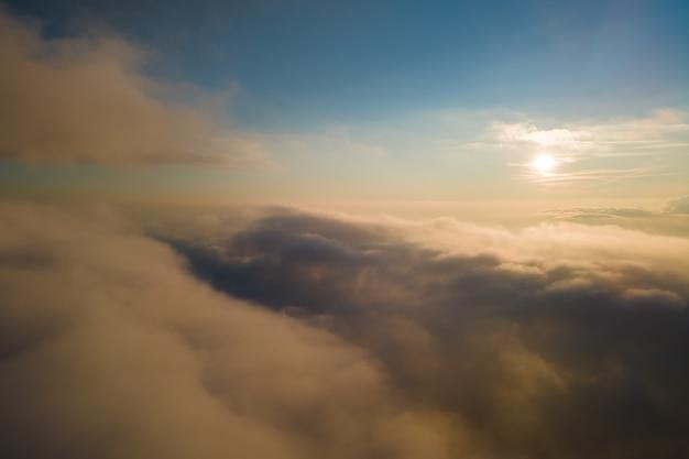 Vista aérea da janela do avião em alta altitude de densas nuvens cúmulos inchados se formando antes da tempestade à noite.
