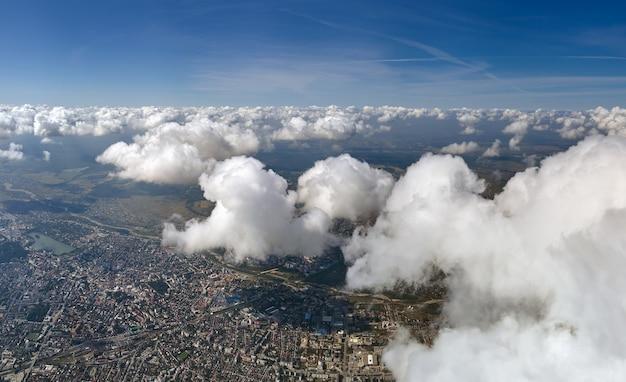 Vista aérea da janela do avião em alta altitude de uma cidade distante coberta com nuvens cumulus inchadas se formando antes da tempestade.
