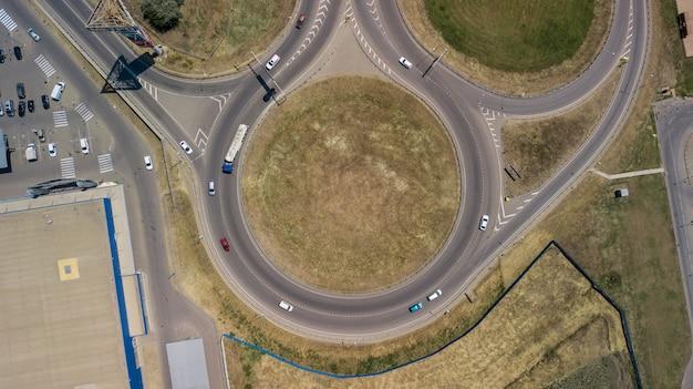 Vista aérea da junção de transporte, vista do dia da junção do tráfego transversal de cima com a estrada do círculo.