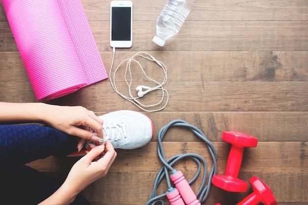 Vista aérea da mulher esportiva amarrando sapato com telefone celular e equipamentos esportivos