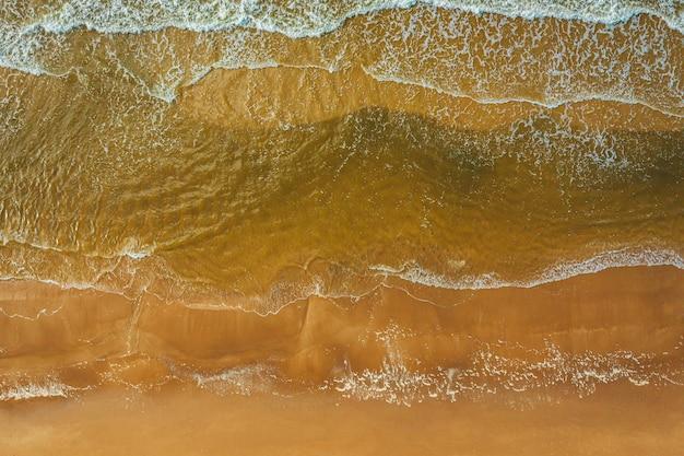 Vista aérea da onda do mar atingindo a costa