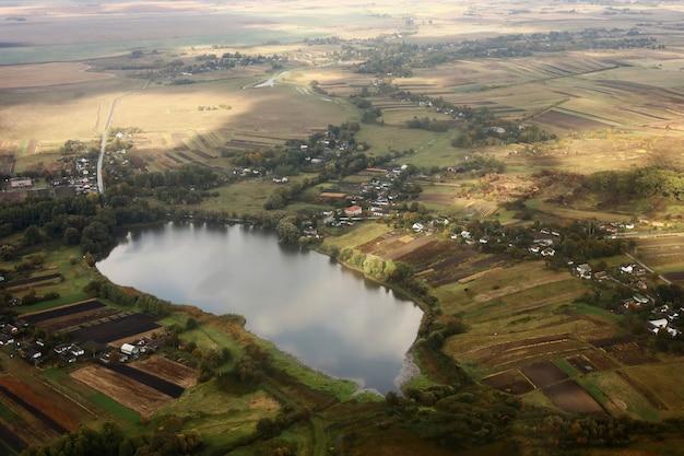 Vista aérea da paisagem da área de terras agrícolas e lago de avião. paisagem com lago.