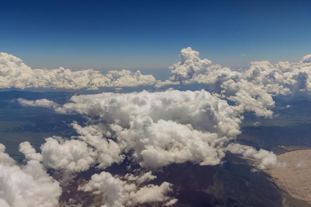 Vista aérea da paisagem das montanhas do arizona em nuvens fofas de avião pela janela