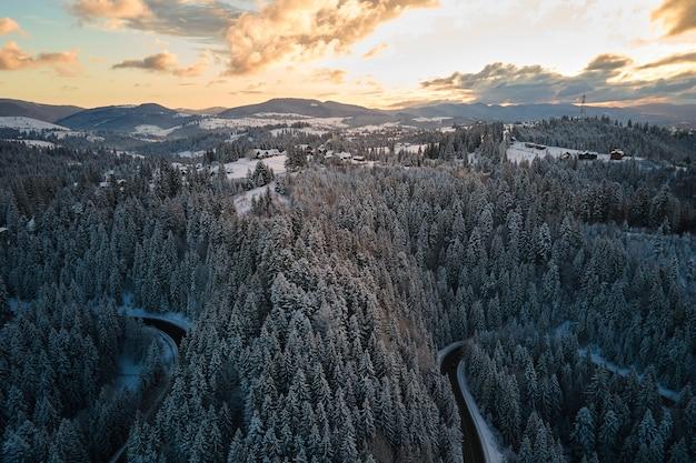 Vista aérea da paisagem de inverno com montanhas cobertas de neve e uma estrada florestal sinuosa na manhã.