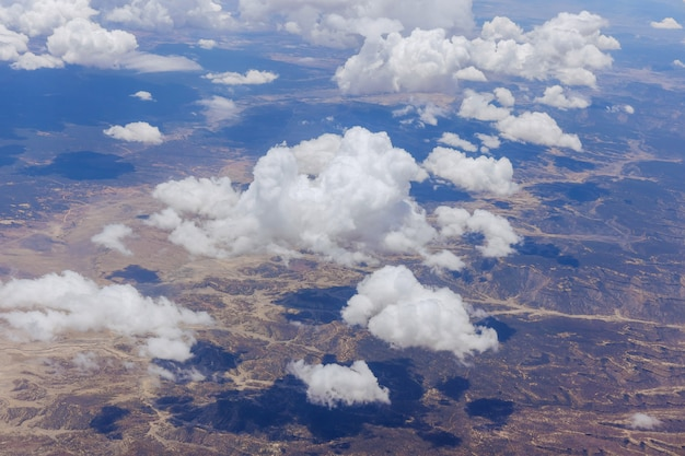 Vista aérea da paisagem de montanhas do deserto do novo méxico em nuvens fofas de avião pela janela