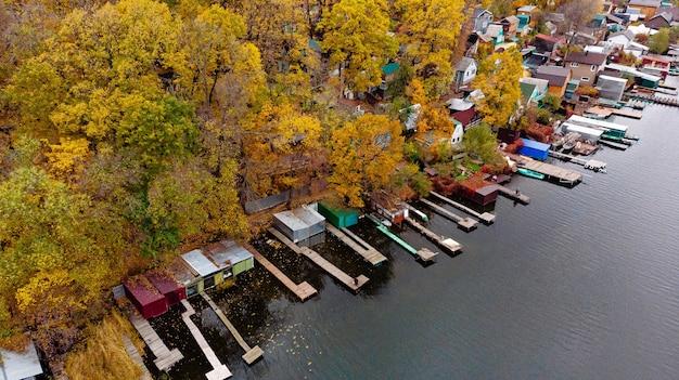Vista aérea da paisagem de outono de uma vila nas margens do rio com passarelas para barcos