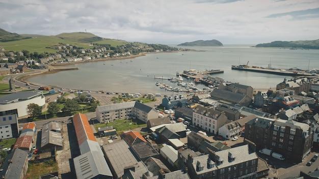 Vista aérea da paisagem urbana da cidade portuária com iates e navios na rua urbana com carros rodoviários dirigindo em