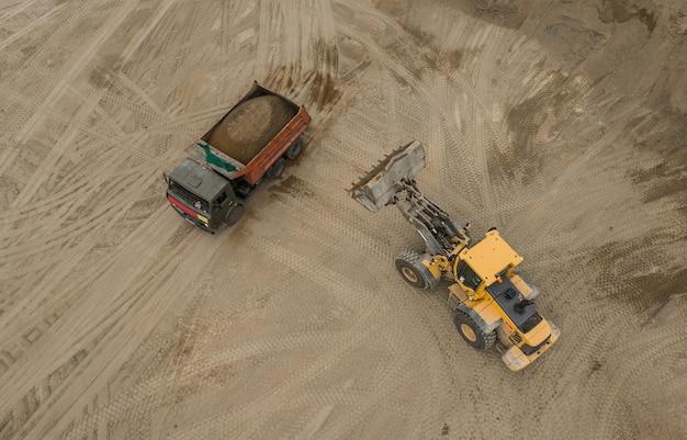 Vista aérea da pedreira de areia. bulldozer despejando areia no caminhão