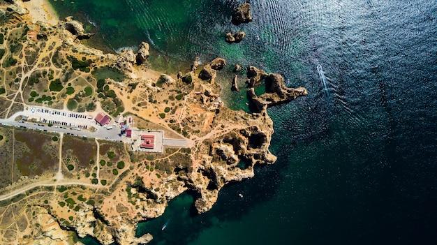Vista aérea da ponta da piedade de lagos, portugal. bela paisagem de falésias íngremes à beira-mar e águas do oceano azul na região do algarve em portugal