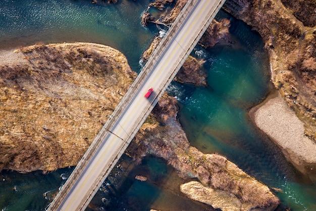 Vista aérea da ponte branca com o movimento do carro vermelho sobre a água azul e ilhas rochosas.