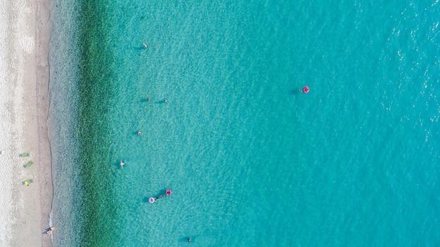 Vista aérea da praia com turistas nadando.