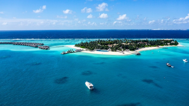 Vista aérea da praia de areia branca da ilha e da lagoa azul no resort das maldivas.