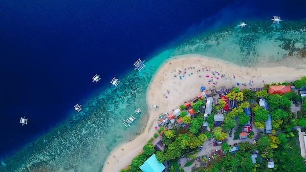 Vista aérea da praia de areia com turistas que nadam na linda água do mar clara da ilha de sumilon, pousando na praia perto de oslob, cebu, filipinas. - impulse o processamento de cores.