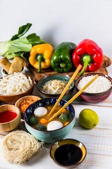 Vista aérea da sopa de bolinho de peixe; arroz; brotos de feijão cenoura e rolinhos primavera com molhos e pauzinhos sobre a mesa