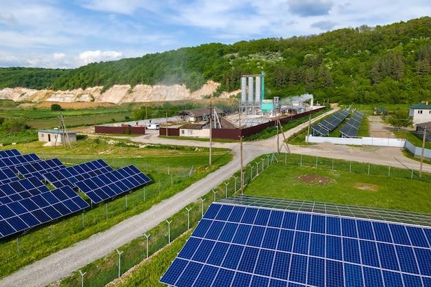 Vista aérea da usina elétrica com fileiras de painéis solares fotovoltaicos para a produção de energia elétrica ecológica limpa na área industrial. eletricidade renovável com conceito de emissão zero.