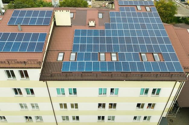 Vista aérea da usina solar com painéis fotovoltaicos azuis montados no telhado do prédio de apartamentos.