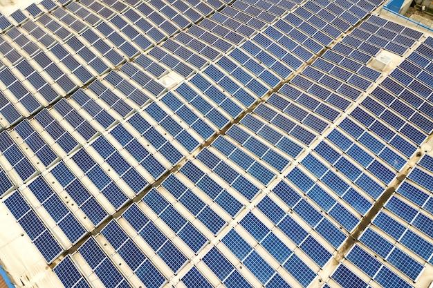 Vista aérea da usina solar com painéis fotovoltaicos azuis montados no telhado do prédio industrial.