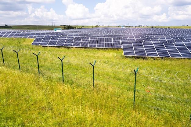 Vista aérea da usina solar em campo verde com cerca de arame protetora em torno dela. painéis elétricos para produção de energia ecológica limpa.
