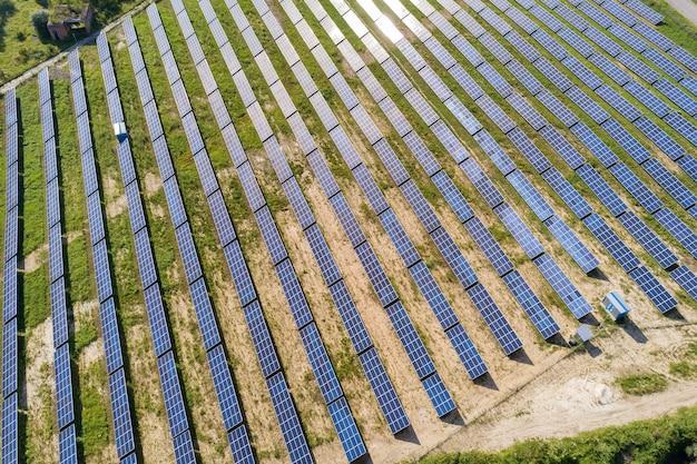 Vista aérea da usina solar em campo verde. fazenda elétrica com painéis para produção de energia ecológica limpa.