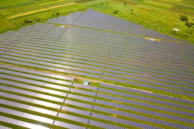 Vista aérea da usina solar em campo verde. painéis elétricos para produção de energia ecológica limpa.
