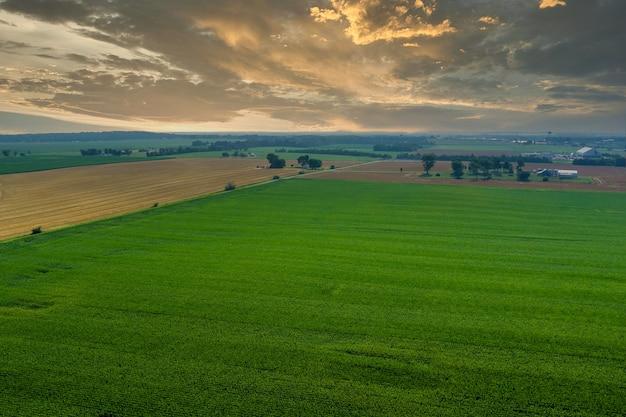 Vista aérea da vila durante o pôr do sol com a luz do sol em campos verdes