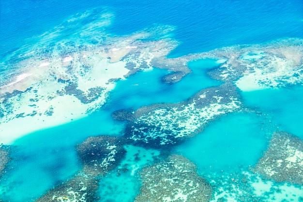 Vista aérea das águas azuis transparentes com recifes de coral e falésias na ilha tropical de seychelles