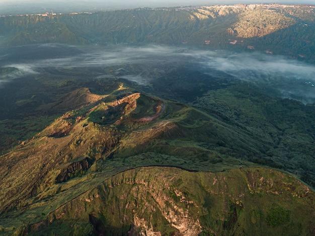 Vista aérea das colinas cobertas de vegetação e neblina sob a luz do sol - perfeita para papéis de parede