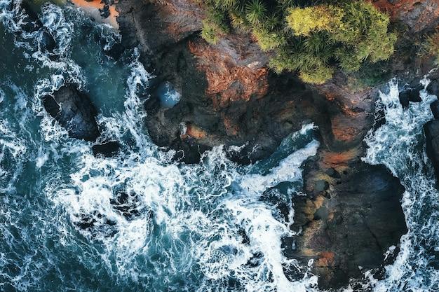 Vista aérea das ondas do mar batendo nas falésias