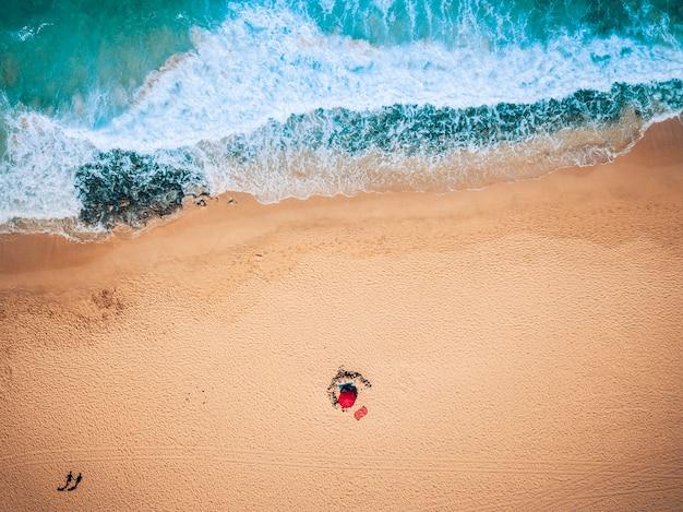 Vista aérea das ondas do mar e da praia de areia com turistas caminhando - conceito de férias de verão com as pessoas - cores azuis e amarelas - lugar tropical com bela natureza e ao ar livre