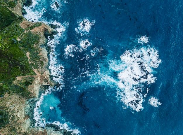 Vista aérea das ondas quebrando na rocha. água azul clara e escura que espuma enquanto ondas quebram na praia. mar profundo.