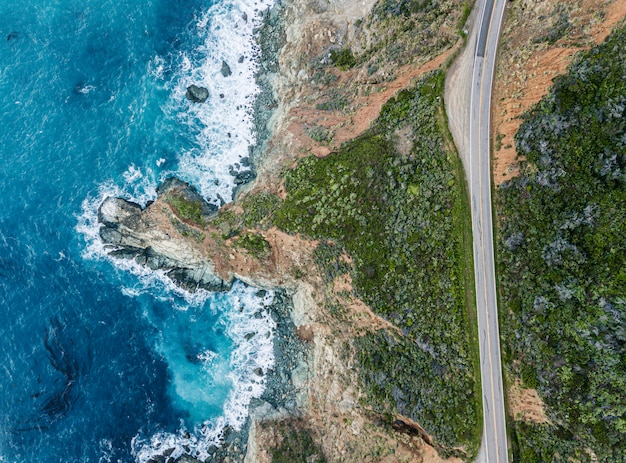 Vista aérea das ondas quebrando na rocha ao lado de uma estrada. espuma de água azul clara e escura enquanto as ondas quebram na praia. mar profundo.