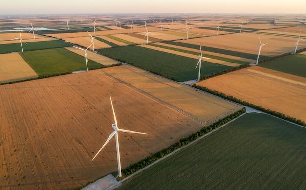 Vista aérea das turbinas de moinhos de vento renováveis, fornecendo a área de cultivo com energia ecológica, obtendo energia do vento que sopra em vasta área de prados agrícolas junto ao mar. eletricidade alternativa