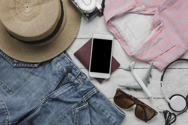 Vista aérea de acessórios que vestem mulheres para viajar com conceito de fundo de tecnologia. itens essenciais para viajantes ou adolescentes e adultos se preparam para a viagem de férias. vários objetos em madeira branca moderna.