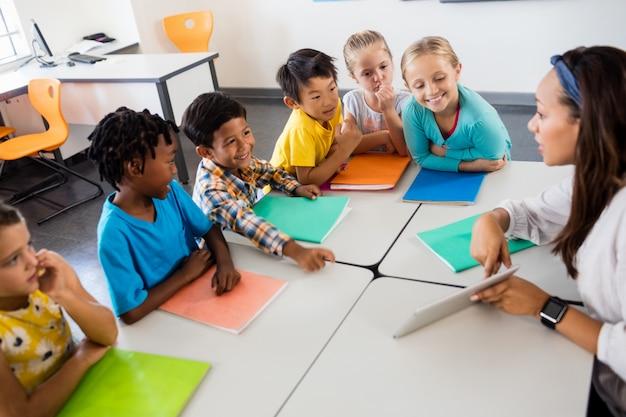Vista aérea de alunos e professor com tablet