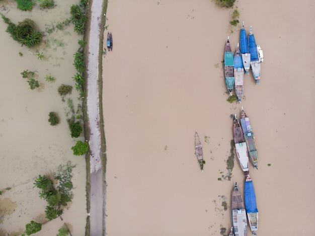 Vista aérea de barcos estreitos de madeira em um rio sujo
