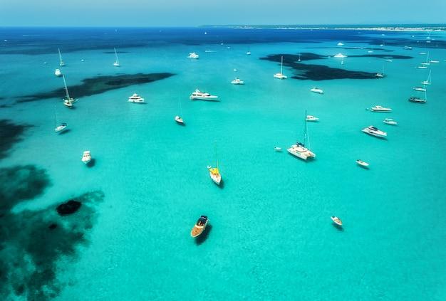 Vista aérea de barcos, iates de luxo e mar transparente em dia de sol