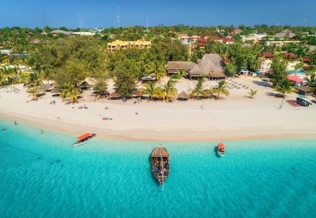 Vista aérea de barcos na costa do mar tropical com praia em dia de sol