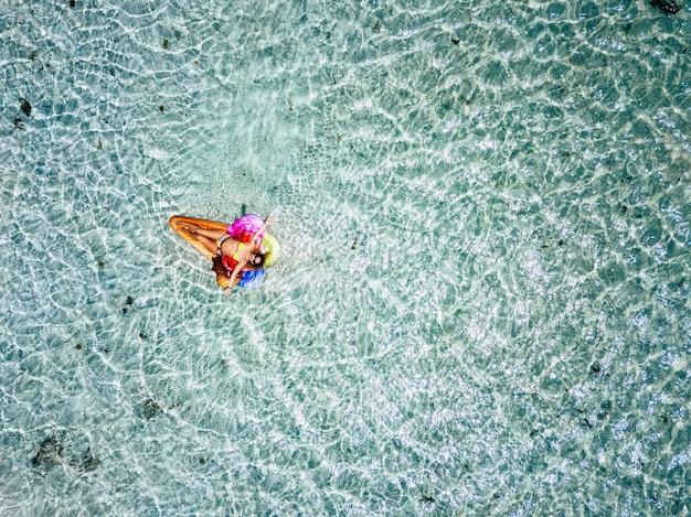 Vista aérea. de belas pessoas caucasianas, mulher adulta, turista, amanhecer e relaxar em um lilo colorido da moda com água do mar tropical transparente e limpa ao redor - conceito de férias de verão e hap