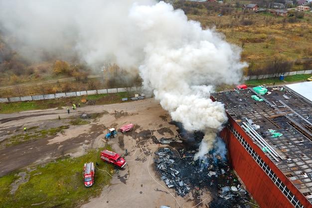 Vista aérea de bombeiros lutando com fogo perto de biulding de fábrica na área industrial.
