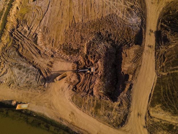 Vista aérea de caminhão e escavadeira ou retroescavadeira trabalhando no canteiro de obras
