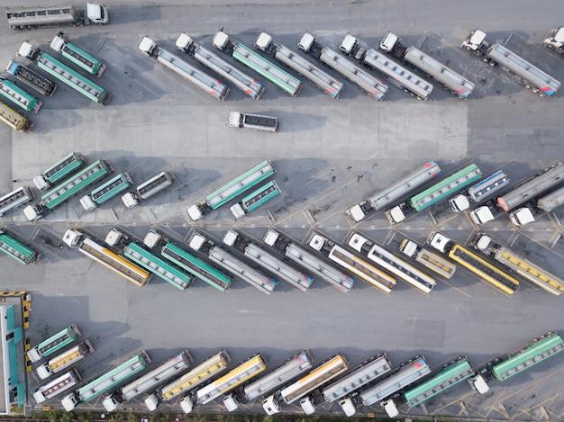 Vista aérea de caminhões de petróleo estão estacionados no estacionamento esperando para transportar o óleo.