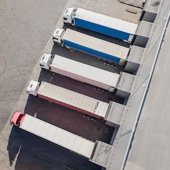 Vista aérea de caminhões descarregando no centro de logostics Foto Premium