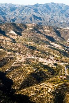 Vista aérea de campos agrícolas em frente a montanhas enevoadas